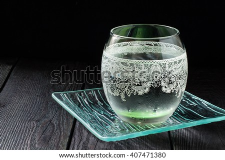 Cold pure mineral water in beautiful glass with ornaments on the dark background  - stock photo