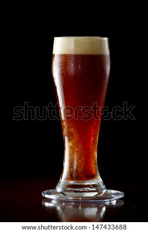 cold red ale served in a cold glass on a dark bar - stock photo