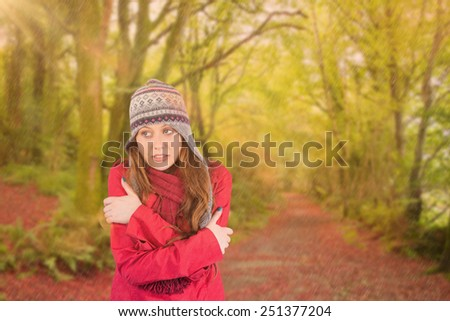 Cold redhead wearing coat and hat against peaceful autumn scene in forest