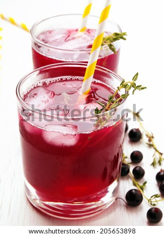 Cold refreshing berry drink with ice and thyme close-up - stock photo