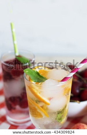 Cold refreshing cocktail with fresh orange, raspberry and mint. Close-up. - stock photo