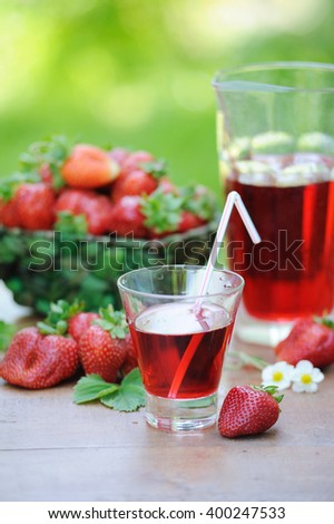 Cold refreshing drink from strawberries in a pitcher and ripe berries in basket on wooden table in the garden
