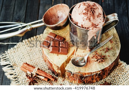 cold refreshing summer dessert , chocolate ice cream with cocoa and cinnamon in an iron mug on a wooden background , rustic style - stock photo