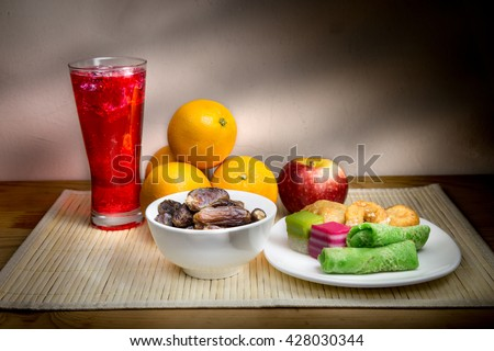 Cold refreshing syrup drinks, sweet dates, kuih are simple and common iftar break fast food during fasting month of Ramadan. Fine art rendition. - stock photo