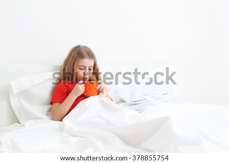 cold sick child laying on bed and drinking a cup of tea - stock photo