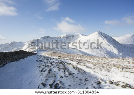 cold snow covered mountain range on a sunny day, helvellyn, cumbria - stock photo
