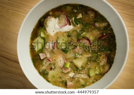 Cold soup of kvass with different herbs, vegetables, and chopped meat  seasoned with sour cream