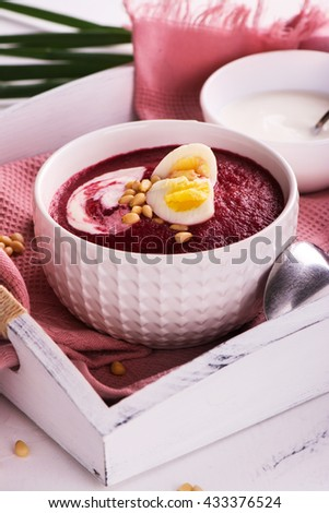 Cold summer beetroot and tomato soup over white wooden tray - stock photo