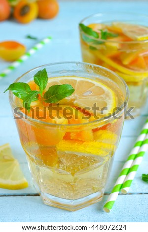 Cold, Summer lemonade with peach and apricot on a blue background