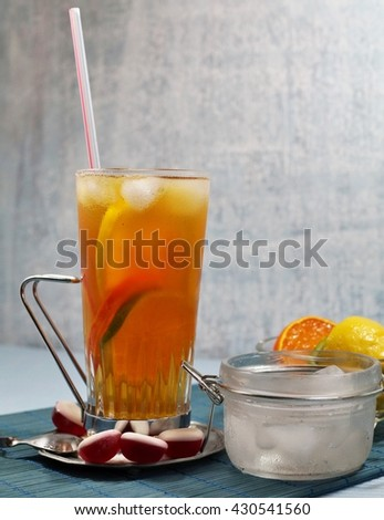 Cold tea with ice cubes and citrus fruits - refreshment on hot days - selective focus - stock photo