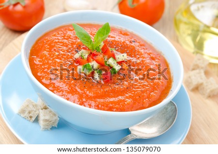 cold tomato soup gazpacho with basil and croutons in a blue bowl, close-up - stock photo