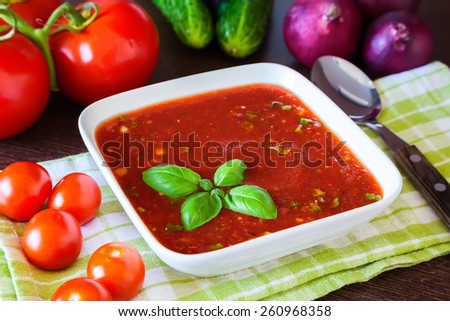 cold tomato soup gazpacho with basil and ingredients wich it has been made of - stock photo