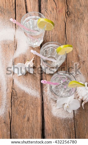 Cold water drinks with ice and a slice of lime on wooden background - stock photo