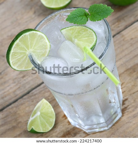 Cold water or lemonade drink with ice cubes and limes - stock photo