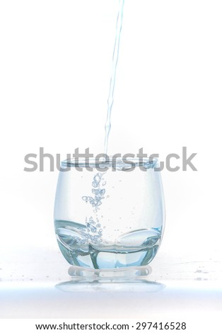 cold water splash on a glass on white background, Ice cubes splashing into glass of water - stock photo