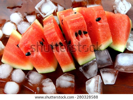 Cold watermelon on ice . watermelons slice on wood background. cool and juicy piece of watermelons. small cut of watermelons on ice.  - stock photo