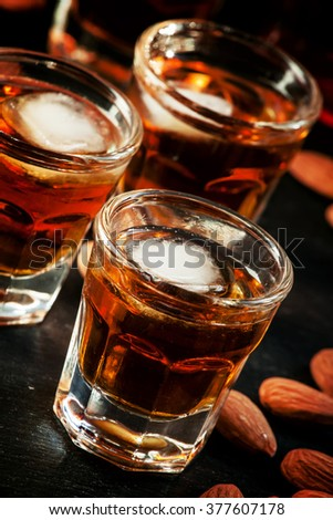 Cold whiskey with ice in a glass and a snack almonds, selective focus