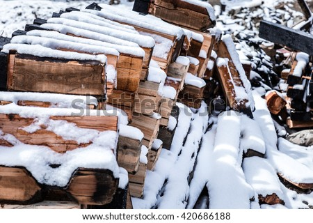 Cold winter background texture pattern with stacked dry chopped firewood logs covered with snow. Chopped logs for winter fire. Firewood pattern - stock photo