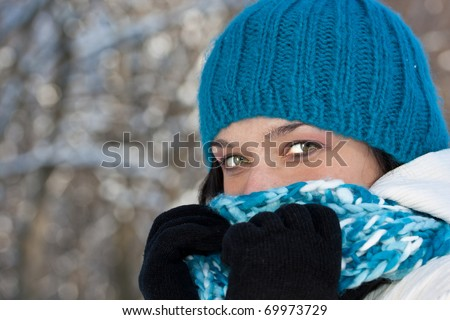 Cold winter woman covering her face in winter forest. - stock photo