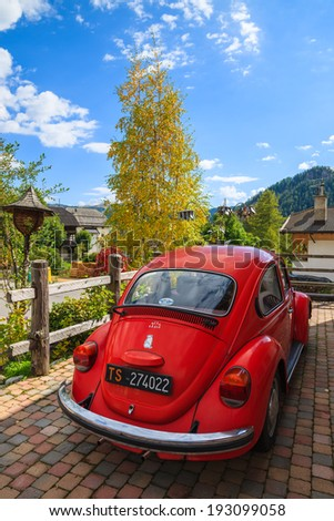 COLFOSCO, ITALY - SEP 26, 2013: Vintage red Volkswagen VW Beetle car parked in front of a house in alpine village Colfosco, Dolomit Mountains, Italy. - stock photo