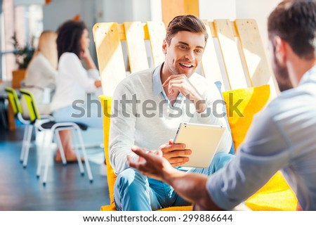 Collaboration is a key to success. Smiling young man holding digital tablet and discuss something with man sitting opposite him in the rest area of the office - stock photo