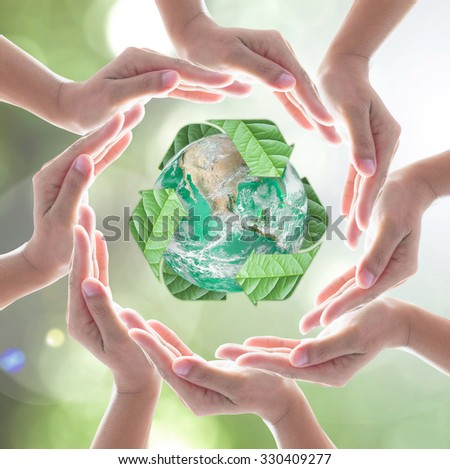 Collaborative human hands surrounding green planet protected by recycled bio sign leaf on blur abstract bokeh background: Recycle, reduce, reuse, CSR idea concept: Element of image furnished by NASA