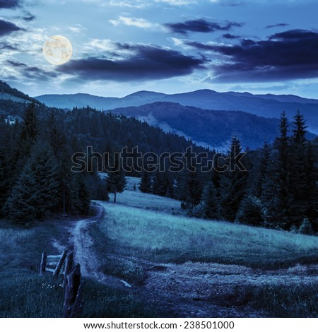 collage landscape. fence near the meadow path on the hillside. forest in fog on the mountain at night in full moon light - stock photo