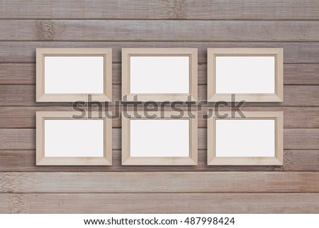 Collage of six blank wooden photo frames on wooden panels wall.