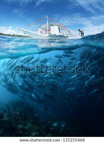 Collage with school of Jack fish underwater and traditional boat on a surface at sunny day - stock photo
