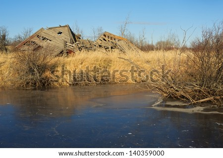 Collapsed barn on the edge of  a small pond.  Surrounded by dry dead grass and willow trees - stock photo