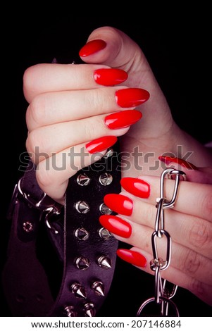 Collar in hand with red painted nails studio shot at black background. - stock photo