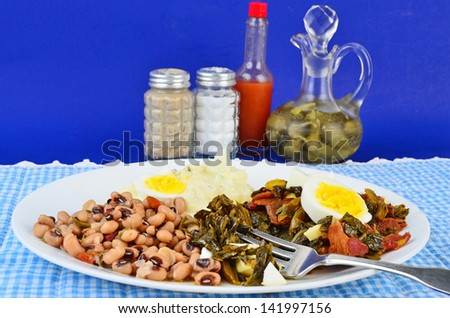 Collard greens seasoned with bacon drippings and salt pork and garnished with boiled egg on white plate with potato salad and black eyed peas.  Blue gingham setting adds to Southern or Soul Food Feel.