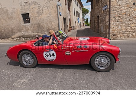 COLLE DI VAL D'ELSA, SI, ITALY - MAY 17: R. De Alessandrini  M. Cerofolini on a vintage Austin Healey 100/4 BN1 (1955) racing in Mille Miglia, on May 17, 2014 in Colle di Val d'Elsa, Tuscany, Italy  - stock photo
