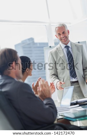 Colleagues applauding the manager during a meeting in the meeting room - stock photo