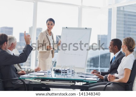 Colleagues asking a question to a businesswoman during a presentation - stock photo