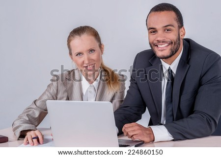 Colleagues at work. Two successful businessman smiling and looking at the laptop while businessmen sitting at a table working on a laptop on a gray background. - stock photo