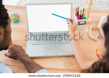 Colleagues brainstorming and pointing laptop screen in the office - stock photo