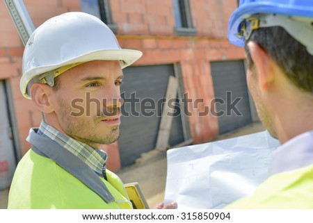 Colleagues checking building plans on site - stock photo