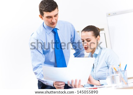colleagues discuss the reports at a desk in the office, working together in business - stock photo