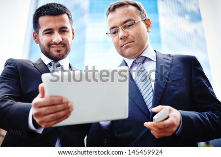 Colleagues discussing business solutions while meeting in urban surroundings - stock photo