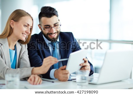 Colleagues discussing data on touchpad - stock photo