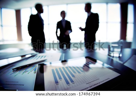 Colleagues discussing their future financial plans, only silhouettes being viewed - stock photo