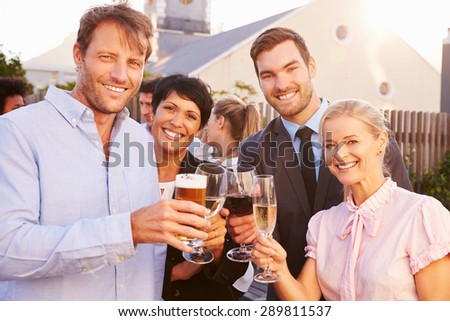 Colleagues drinking after work at a rooftop bar