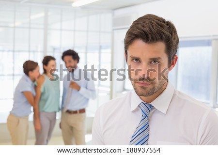 Colleagues gossiping with sad young businessman in foreground at a bright office - stock photo