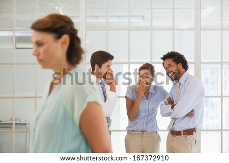 Colleagues gossiping with sad young businesswoman in foreground at a bright office - stock photo