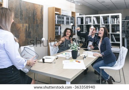 Colleagues having fun in office and throwing papers in a basketball competition - stock photo