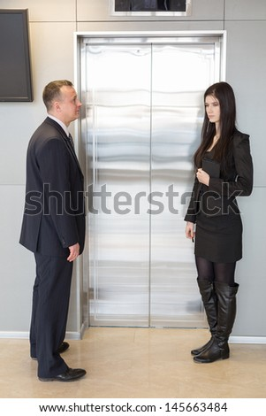 Colleagues in business suits waiting for elevator - stock photo