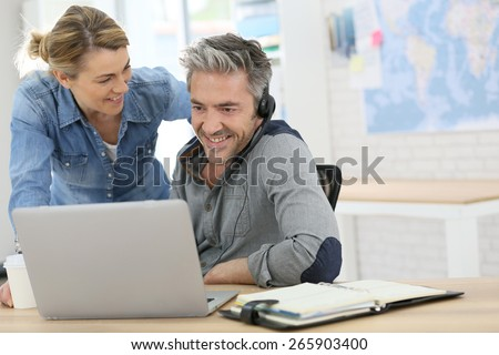 Colleagues in office working on laptop computer - stock photo