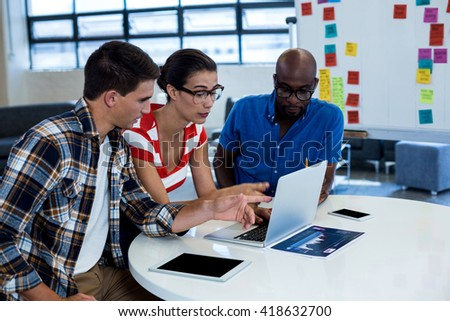 Colleagues interact using laptop at their desk in the office - stock photo