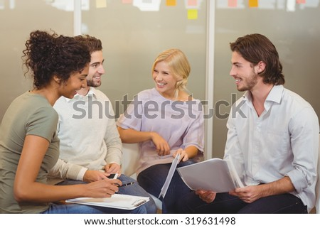 Colleagues interacting with each other in meeting at creative office - stock photo